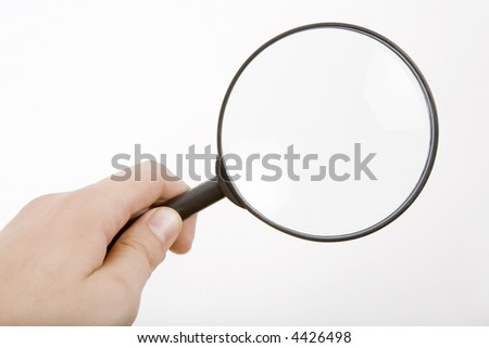 The hand holds a magnifier
