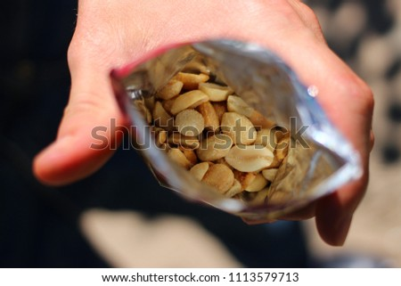 The hand holds a packet of peanuts - Shutterstock ID 1113579713