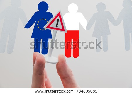 The hand holds a sign with a warning between the European and the Polish Union. Crisis in Poland. Problems between the European Union and the Polish Union. European Union is threatening Poland. #784605085