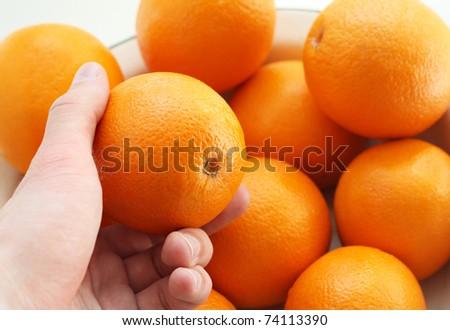 The hand holds an orange. A choice of a ripe orange