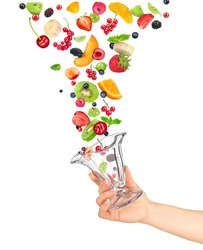the hand holds the glass bowl of fruit salad and the ingredients in the air isolated on white background