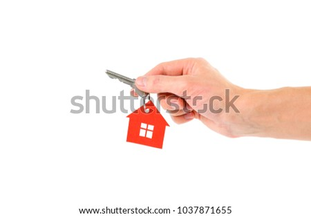 The hand holds the keys with the red house keychain. Purchase of apartments. House in hands. Close up. Isolated on a white background.