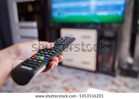 The hand holds the remote control and changes channels on the TV