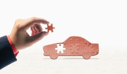 The hand inserts the last piece into the car-shaped puzzle. Car buying, repair, warranty service. Concept.