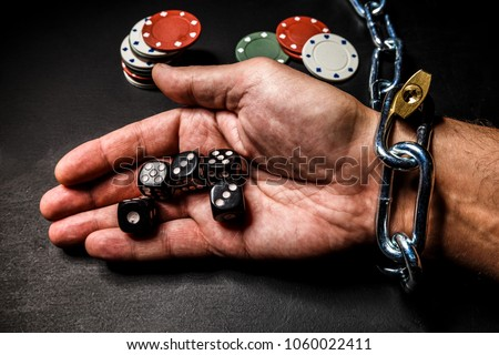 The hand is chained to the chain as a dependence on gambling. The photo can illustrate materials about the effects of gaming addiction. #1060022411