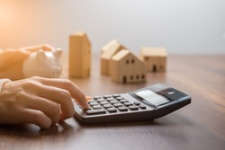 The hand is pressing calculators, piggy bank with wooden house. buy or rent question on note with calculators on desk. Save money and buy house concept.