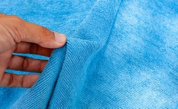 The hand is touching the blue synthetic fur. Synthetic fabric texture background for design.