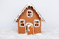 The hand-made eatable gingerbread house and snow decoration on red background
