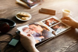 the Hand man holding a family photo album  against the background of the a wooden table
