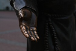 The hand of a bronze statue on the skyline