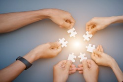 The hand of a businessman holding a paper jigsaw And solve the puzzle together. The business team assembled a jigsaw puzzle. A business group wishing to bring together the puzzle pieces
