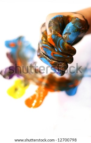 The hand of a child. Fingers overcast with marbeling color from painting on white background.
