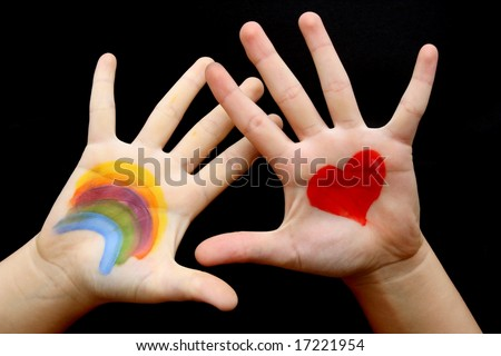 The hand of a child painted with rainbow and red heart