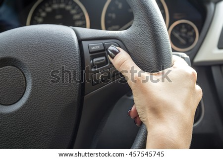 The hand of a girl with a stylish manicure lies on the handlebars in a saloon car. #457545745