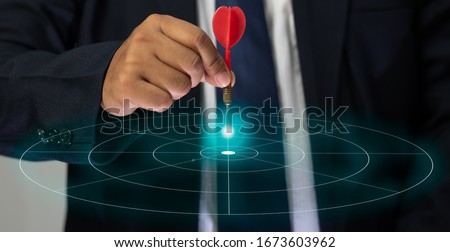 The hand of a male businessman holding a dart and aimed at the graphic target, Targeting the business concept.