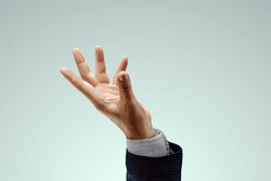 The hand of a man in a business catches something. Stock for business concept. Close-up, copy space