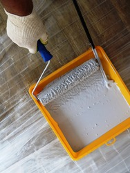 the hand of a painter with a blue roller picks up gray paint from a yellow substrate top view, a tool for painting surfaces in the process, repair of a room with painting walls
