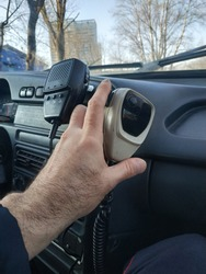 The hand of a policeman holds the tangent of a radio station. Inside the company car.