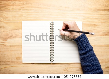 https://image.shutterstock.com/display_pic_with_logo/180537128/1051295369/stock-photo-the-hand-of-a-woman-writing-a-book-on-a-wooden-desk-top-view-1051295369.jpg