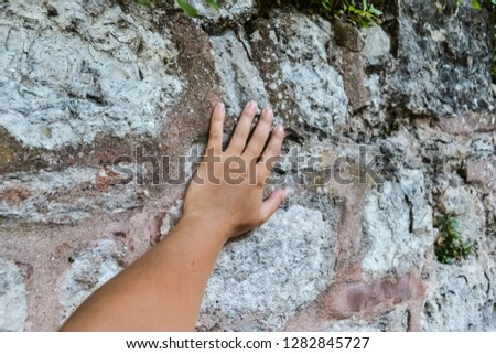 the hand of a young white woman touches the wall. touch the antiquity. #1282845727