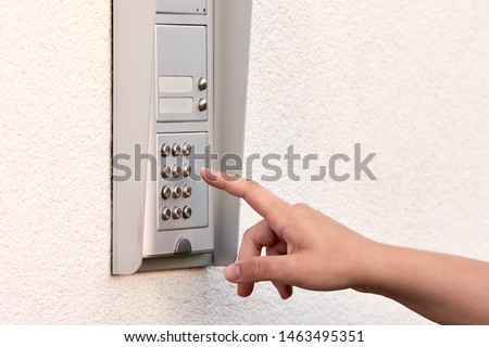 The hand of a young woman enters a numeric code on the keypad of an electronic lock or doorbell. #1463495351