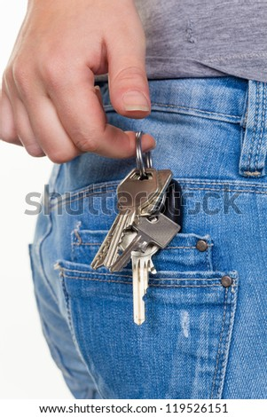 the hand of a young woman in jeans with keyring. key for car and home