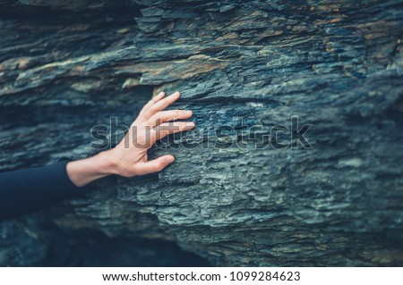 The hand of a young woman touching a rock surface #1099284623
