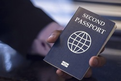 The hand of an African immigrant holds a second passport, resettlement