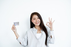 The hand of an Asian woman holding a credit card is used for online shopping and Internet payments.