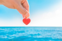 The hand of man holds a red little castle in the form of a heart close-up against the blue sea and the sky with a horizon line. Symbol or sign of love.