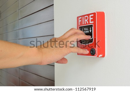 The hand of man is pulling fire alarm on the wall next to the door