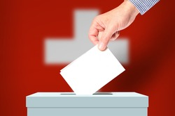 The hand of man putting his vote in the ballot box with flag Switzerland on background. Election in Switzerland