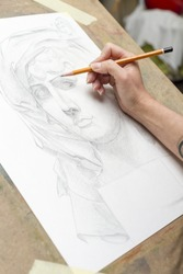 The hand of the artist with a pencil, drawing a portrait.