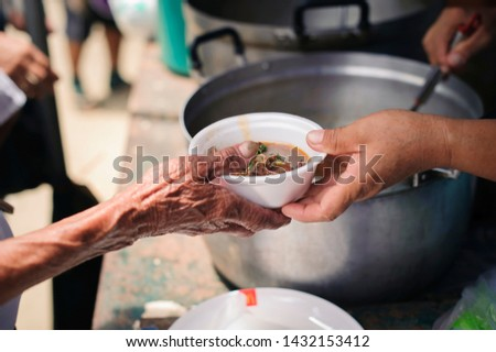 The Hand of the Beggars receives charity food from fellow human beings : The concept of humanitarianism : The hands of refugees have been aided by charity food to alleviate hunger : Feeding Concepts