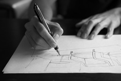 The hand of the designer with a pen, designing and sketching a furniture product in monochrome