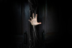 The hand of the man holding the stick from the wooden door from the inside of the dark room
