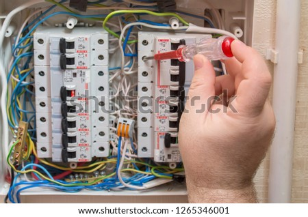 The hand of the master checks the phase in the network with an indicator screwdriver.