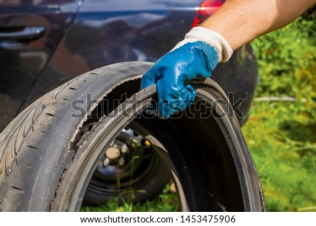 the hand of the master in a blue glove holds the torn tire. tire repair, tire repair. in the background black car in blur #1453475906