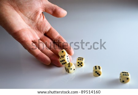 The hand of the person throwing cubes for dicing.