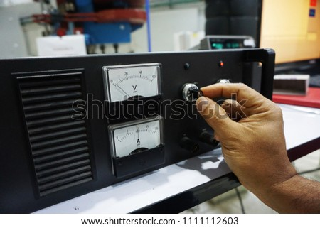 The hand of the technicians tune that the power supply                                #1111112603