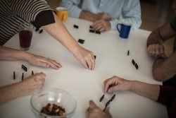 The hand of the victor. Senior people playing dominoes  at home. Focus is on hands.