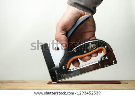 the hand of the worker uses an steel industrial stapler. industrial stapler nailing  the leather to the wood by the staple isolated on white background