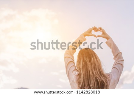 The hand-painted girl's silhouette is a heart-shaped symbol of love, compassion, and friendship with beautiful tranquility on a sunny background in the morning of winter in Thailand. Love concept