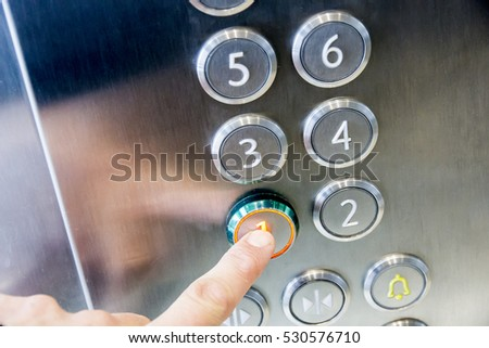 The hand presses on the first floor elevator button