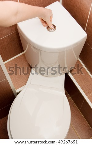 The hand presses the toilet bowl button