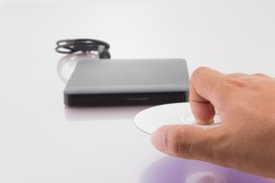 The hand puts a disk in the  external CD DVD,  external CD DVD burner writer over white