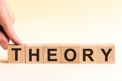 The hand puts a wooden cube with the letter T from the word THEORY. The word is written on wooden cubes standing on the yellow surface of the table.