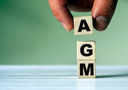 The hand puts the cube block with the inscription AGM. Annual general meeting - acronym on wooden cubes