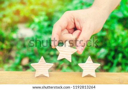 The hand puts the third star on a green background. Quality assessment and popularity. Overview of the restaurant or hotel. Awarding the highest score, recognition and praise. Success and luck. #1192813264