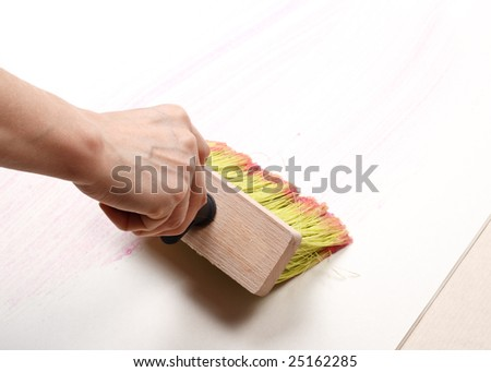 The hand smearing wall-paper by glue. Home renovation. - stock photo
